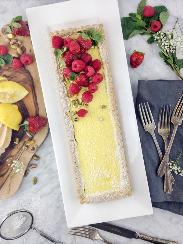 aerial view of a rectangular lemon tart on a white plate, with raspberries and strawberries on top, and some squeezed lemon halves and fresh berries on a wood board on the left side. Antique forks on a grey napkin, and fresh mint leaves and berries, on the right side