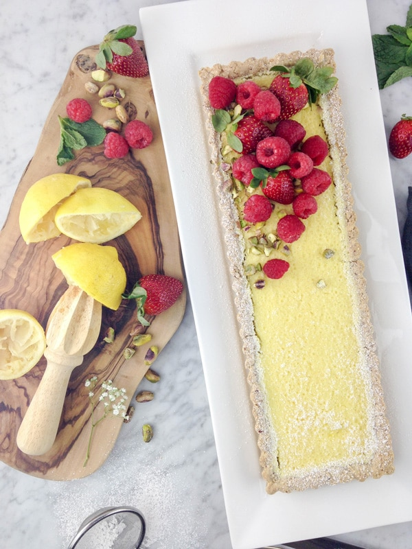 aerial view of a rectangular lemon tart on a white plate, with raspberries and strawberries on top, and some squeezed lemon halves and fresh berries on a wood board on the left side