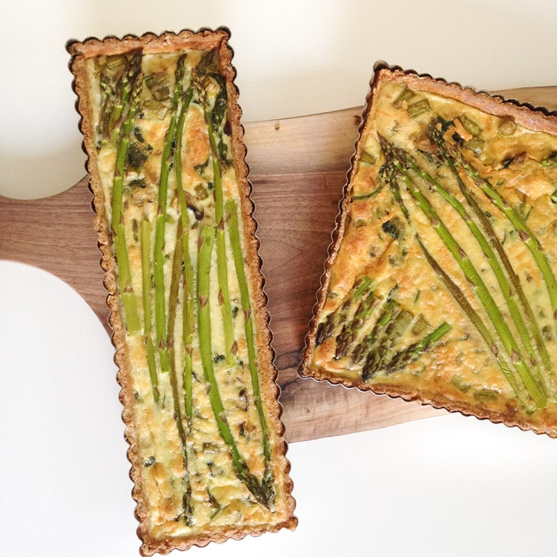 aerial view of 1 thin rectangular quiche and 1 square quiche on top of a walnut cutting board and white background, both quiches have asparagus baked on top