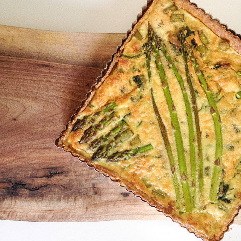 aerial view of a square quiche with baked asparagus on top, sitting on top of a walnut cutting board and white background