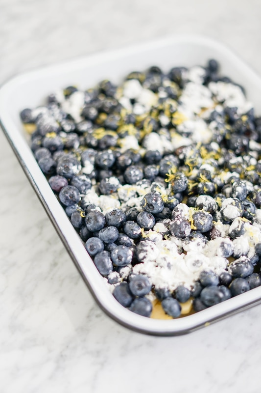 close-up of a large baking pan with fresh blueberries sprinkled with corn starch and lemon zest