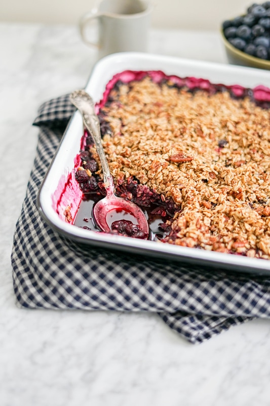 vertical close-up view of a large pan of blueberry crumble with a portion taken out and a blue checkered towel around